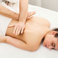 Hands massaging female back and shoulders. Professional body treatment or relaxation procedure at spa salon. Health care, beauty and wellness concept.